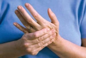 A woman holding her hand from nerve pain