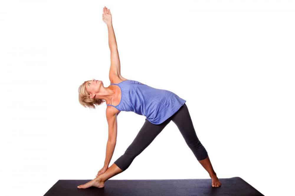 A woman doing the yoga Triangle Pose known as Trikonasana