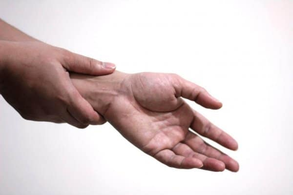 A woman trying to relieve her peripheral neuropathy pain by massaging her hand